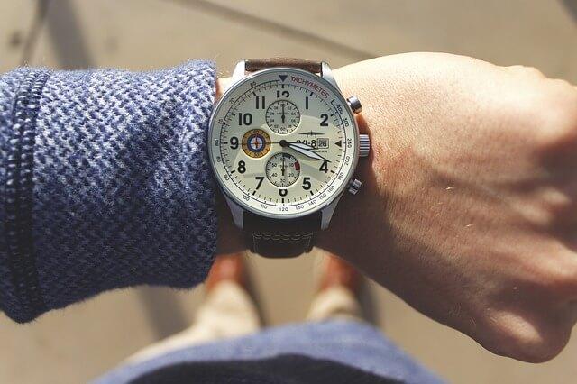 腕時計で時間を確認する人