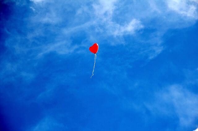青空を飛ぶ赤いハート型の風船